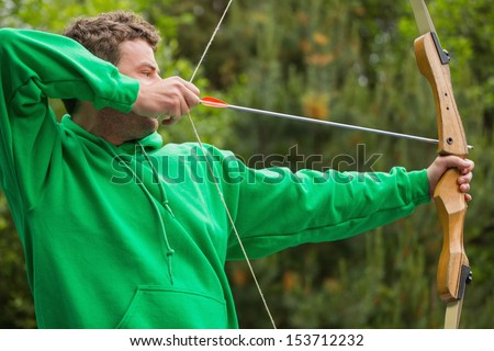 Man in green jumper about to shoot arrow at the archery range - stock photo
