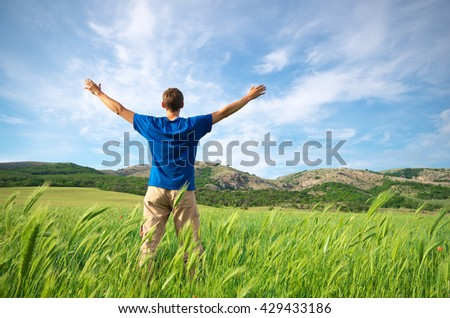 Man in green meadow and sunshine. Conceptual design. - stock photo