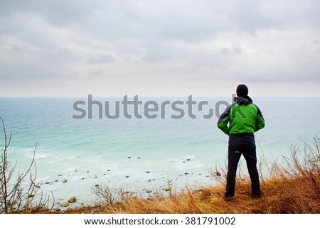 Man in green windcheater stand on cliff above bay and look at sea far horizon. Windy cold weather at ocean. Vivid and vignetting effect.