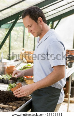 Man in greenhouse putting soil in pot - stock photo