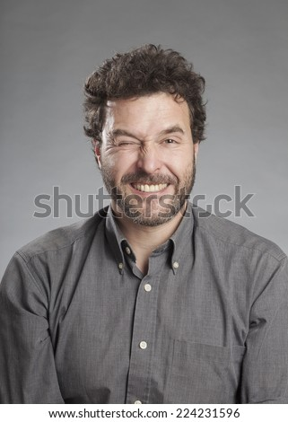 Man in grey shirt pulling funny face