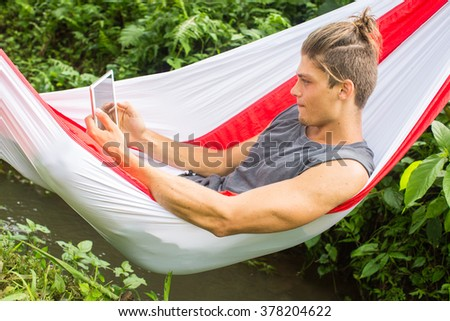 Man in hammock working on laptop during summer holidays. - stock photo