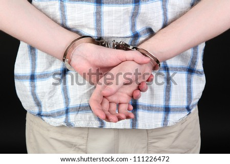 man in handcuffs on black background close-up