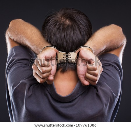 Man in handcuffs with hands on neck on gray background - stock photo