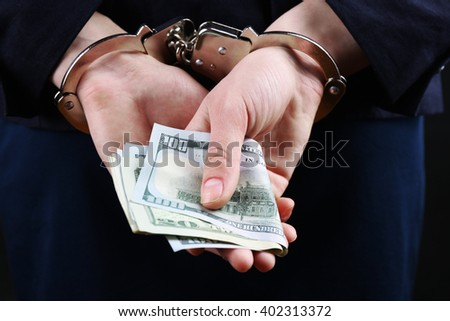 Man in handcuffs with money - stock photo