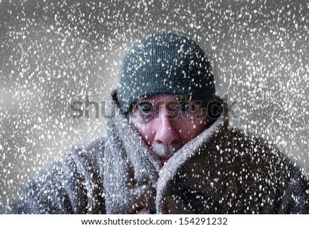 Man in hat and coat shivering in Christmas snowstorm with cloudy skies and snowflakes blowing in wind funny - stock photo