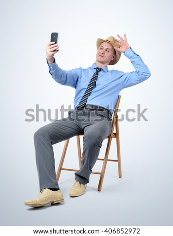 Man in hat and tie makes selfie sitting on a chair - stock photo