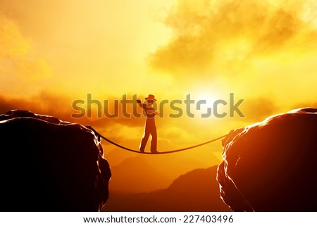Man in hat walking and balancing on rope over precipice in mountains at sunset. Concept of business, risk taking, challenge, concentration. - stock photo