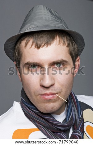 Man in hat with toothpick in his mouth
