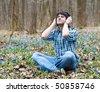 Man in headphones meditate in spring wood - stock photo