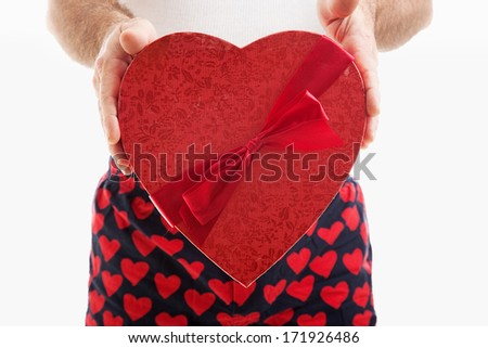 Man in hear underwear holding a big red Valentines Day heart filled with chocolate candy.  White background.   - stock photo