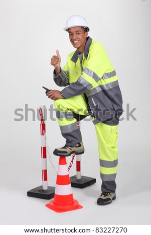 Man in high visibility overalls with a traffic cone and barrier - stock photo