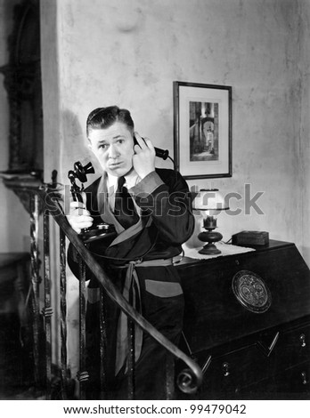 Man in his apartment listening on his telephone