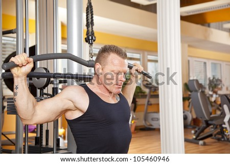 man in his forties training latissimus in gym - stock photo
