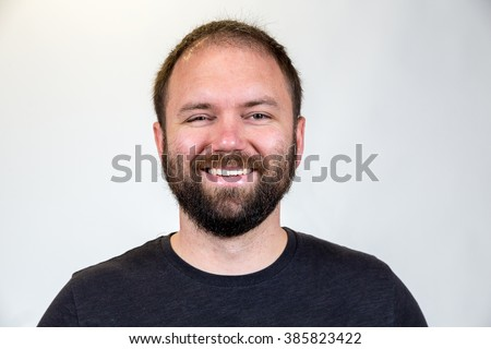 Man in his mid-30's poses for a studio portrait with a semi white background. - stock photo