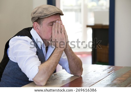 man in his 50's sitting at table and looks tired - stock photo