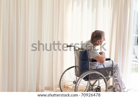 Man in his wheelchair looking out the window - stock photo
