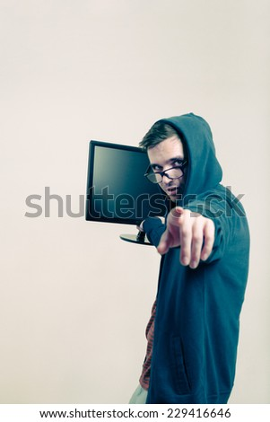 Man in hoodie holding monitor and pointing at you. - stock photo