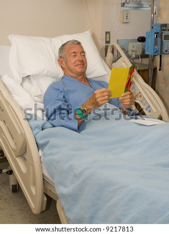 Man in hospital bed reading a get well card - stock photo
