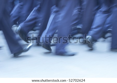 Man in identical suites walking throught street. Cold lighting. Blurred. - stock photo
