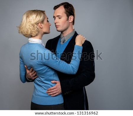 Man in jacket embracing woman in blue cardigan isolated on grey - stock photo