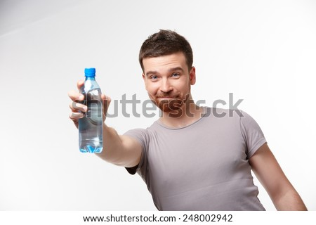 man in jeans and a T-shirt with bottle of water  - stock photo