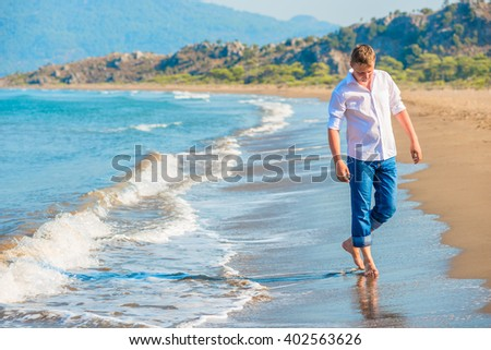 man in jeans and a white shirt walking along the seashore - stock photo