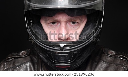 Man in leather jacket wearing motorcycle helmet on black background. - stock photo