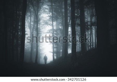 man in light spot in dark forest - stock photo