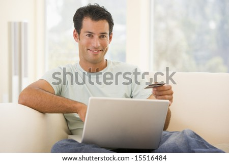 Man in living room using laptop and holding credit card smiling - stock photo