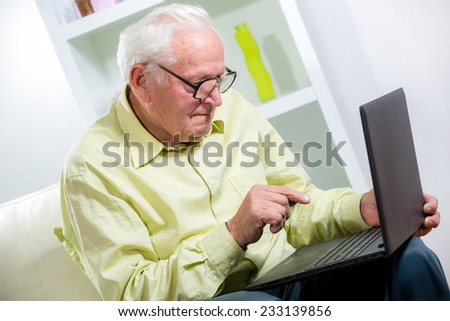 Man in living room with laptop  - stock photo