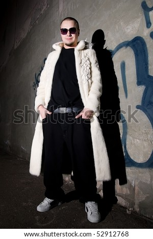 Man in long white fur coat posing like a pimp near the grungy  wall at night - stock photo
