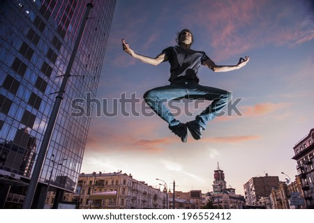 Man in lotus position over the city. - stock photo