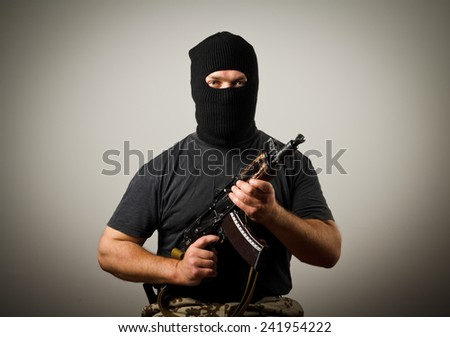 Man in mask with gun - stock photo