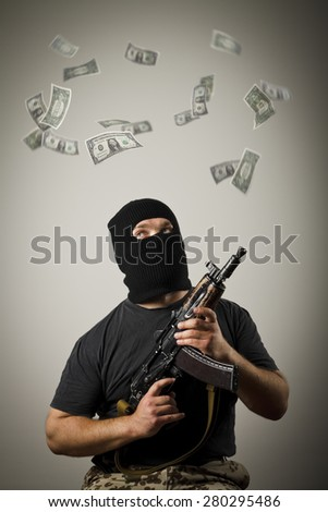 Man in mask with gun and falling dollar banknotes.  - stock photo