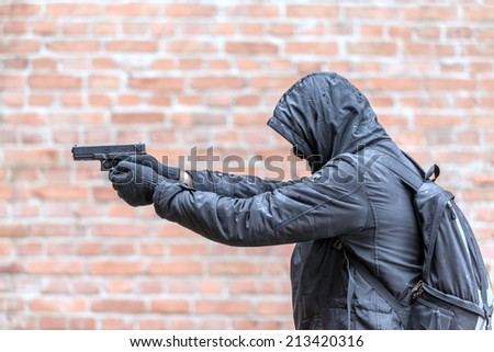 man in mask with handgun - stock photo