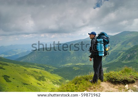 Man in montains with binocular and back pack look - stock photo