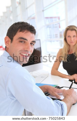 Man in office signing contract