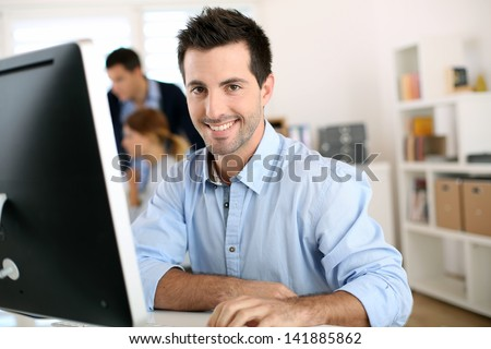 Man in office working on desktop computer - stock photo