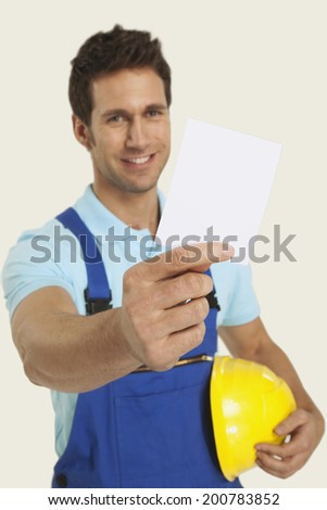 Man in overall holding blank paper and hardhat smiling - stock photo