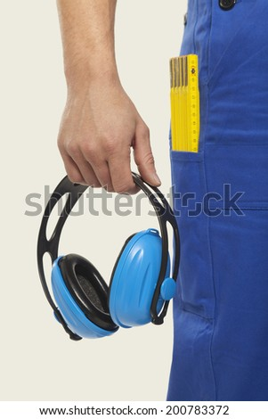 Man in overall holding ear muff mid section close-up - stock photo
