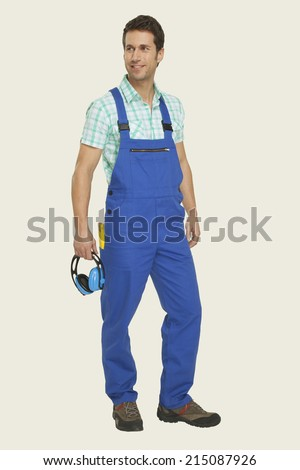 Man in overall holding ear muff smiling - stock photo