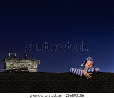 man in pajamas climbing on the roof - stock photo
