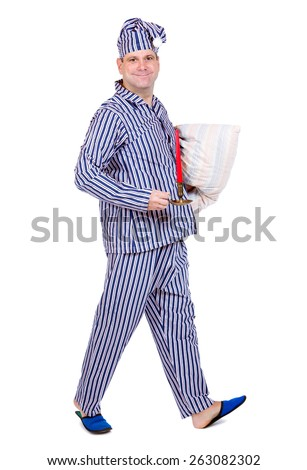 man in pajamas with pillow and candle walking on white background - stock photo