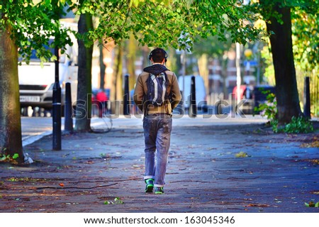Man in park silhouette with headphones - stock photo