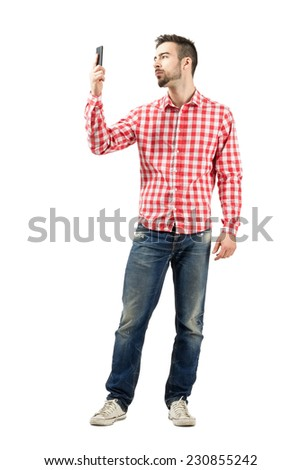 Man in plaid shirt checking his smart phone. Full body length portrait isolated over white background.  - stock photo