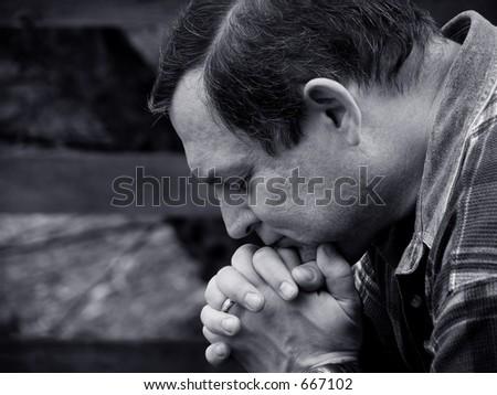 Man in prayer black and white version - stock photo