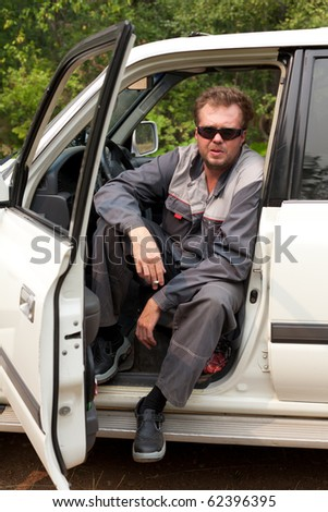 Man in protective clothing sitting and smoking - stock photo