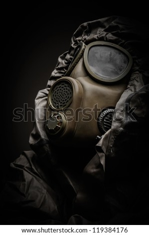 Man in protective suit against dark background - stock photo