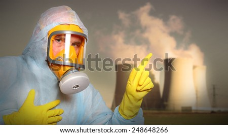 Man in protective suit with gas mask alerting against air pollution. - stock photo